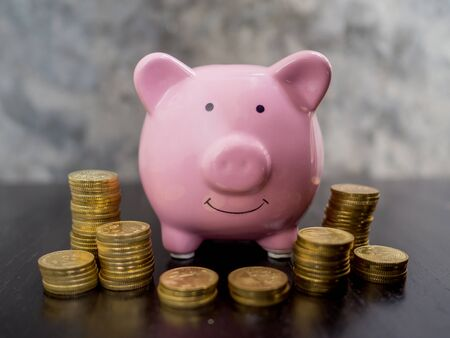 pink piggy bank with coins pile on black cement wall background, Saving money for future plan and retirement fund concept. Banco de Imagens