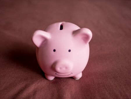 pink piggy bank on dark red background, Saving money for future plan and retirement fund concept. Banco de Imagens