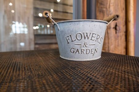 Flowers & Garden metal bucket on iron shelf.