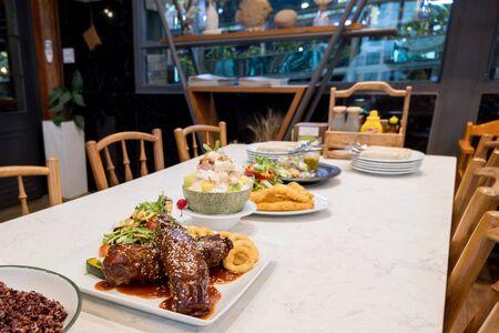 Steaks, Organic vegetables salads and fruit salad are prepared on the food table.