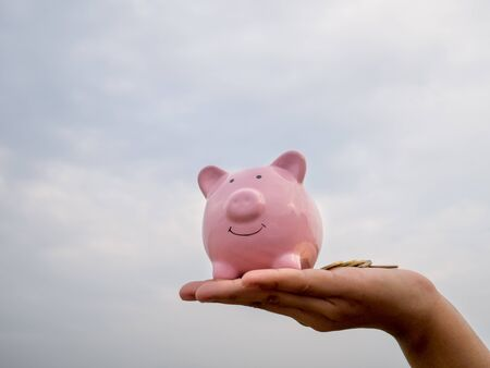 hand holding pink piggy bank on the blue sky with cloud background, Saving money for future plan and retirement fund concept.