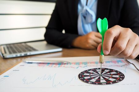 Trader woman holding a darts aiming at the target center of dart board, Setting challenging trading goals And ready to achieve that concept.