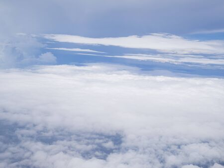 Clouds from airplane window with blue sky.