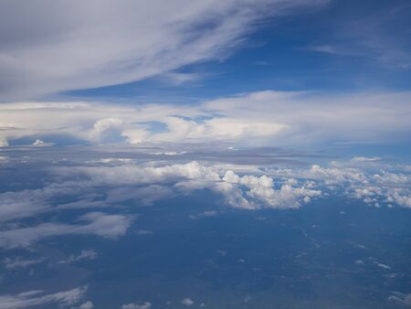 Clouds from airplane window with blue sky and high angle ground. 版權商用圖片