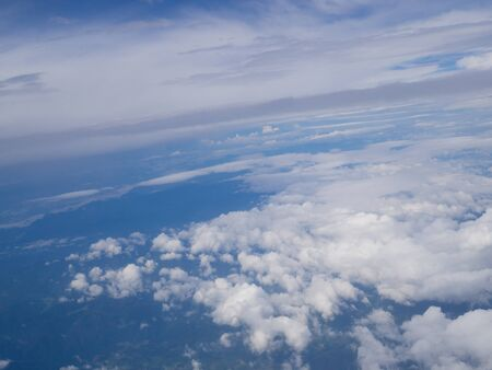 Clouds from airplane window with blue sky and high angle ground. Archivio Fotografico