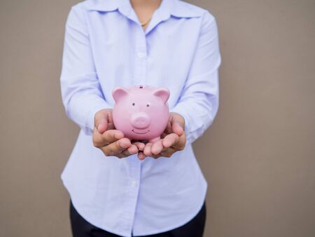 Business hand holding pink piggy bank on brown cement wall background, Saving money for future plan and retirement fund concept. Imagens