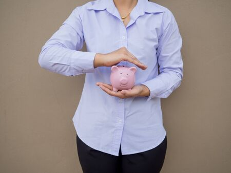Business hand prevent pink piggy bank on brown cement wall background, Saving money for future plan and retirement fund concept. Imagens
