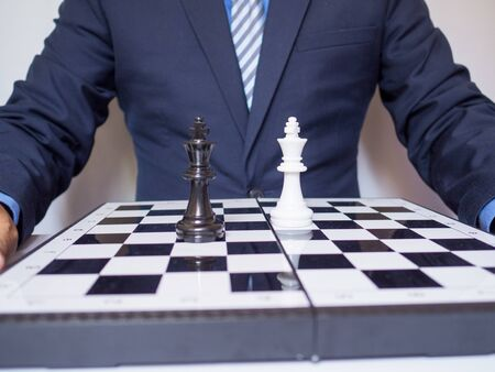 Businessman with two king on chess board, challenges planning business strategy to success concept.