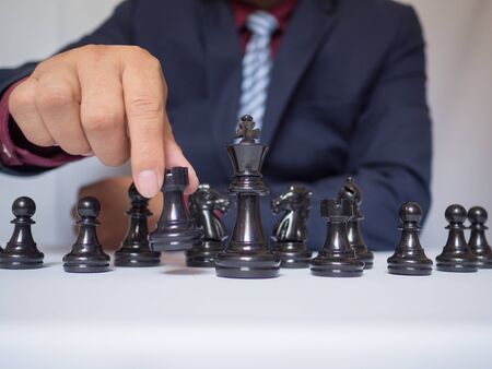 Businessman hand moving chess piece with white background, challenges planning business strategy to success concept.