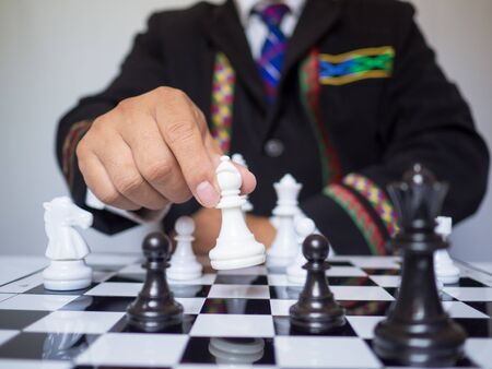 Businessman hand moving chess piece on board with white background, challenges planning business strategy to success concept. 免版税图像