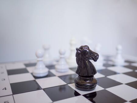A black knight chess stand in front of white chess enemy on board, challenges planning business strategy to success concept.