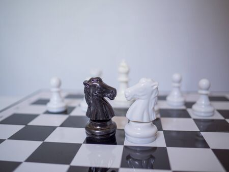 A black and white two knight chess are stand in front of white chess enemy on board, challenges planning business strategy to success concept.