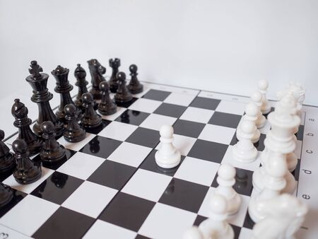 Black and white chess-Army are standing on a board with white background, challenges planning business strategy to success concept.