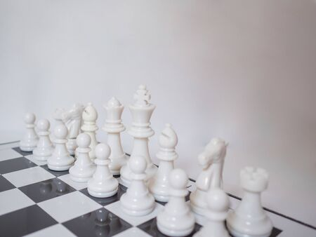 A white chess-Army is standing on a board with white background, challenges planning business strategy to success concept.