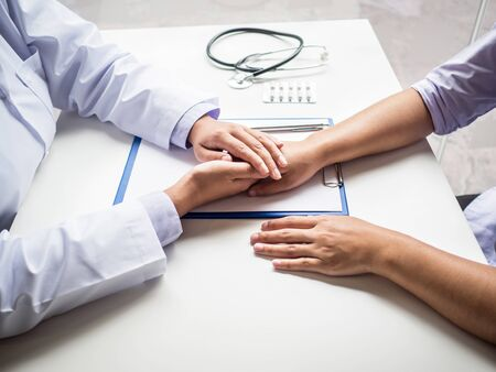 The doctor holding hands to encouragement and explained the health examination results to the patient.