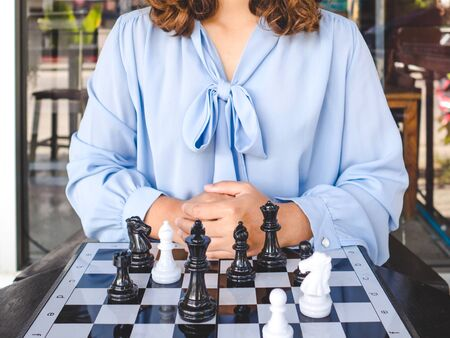 Businesswoman and chess pieces on board, challenges planning business strategy to success concept.