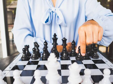 Businesswoman hand moving chess piece on board, challenges planning business strategy to success concept.
