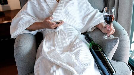 Woman hand holding a glass of wine and smartphone with wine bottle on the sofa.
