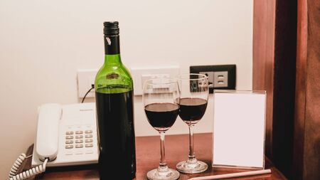 Two glasses of wine and wine bottle with phone on the wooden table.