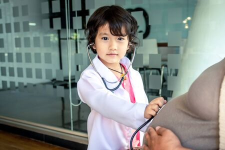 Photo of kid doctor and stethoscope with pregnant mother in the office.