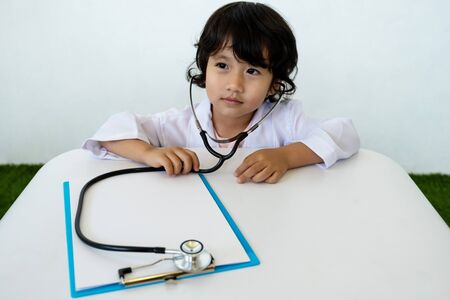 Photo of stethoscope with kid doctor and clipboard on white background.