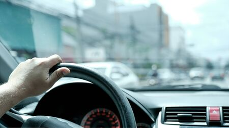Photo of the hand is controlling the steering wheel. Stock Photo