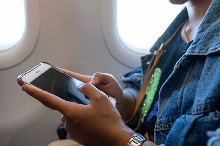 The woman's hand sitting by the window on the plane playing smart phone.
