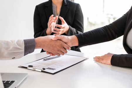 Shaking hands and clap after office executives are interviewing job applicants in the meeting room.