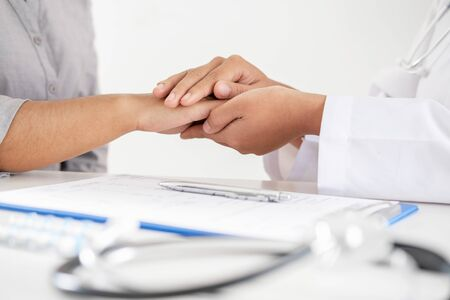 Doctor holding hands to encouragement and explained the health examination results to the patient. Stock fotó