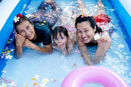 Three generation people swimming in Inflatable Pool at the summer time.
