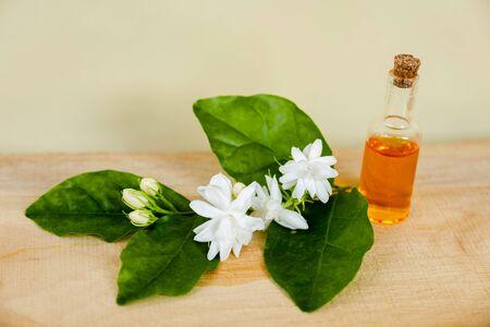 Jasmine oil, Jasmine flower, Jasmine perfume on wooden background, spa aromatherapy.