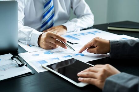 businessmen and businesswomen team pointing to charts meeting to plan strategies to increase business income. Have a brainstorming graph analysis and discussing for the new target success.