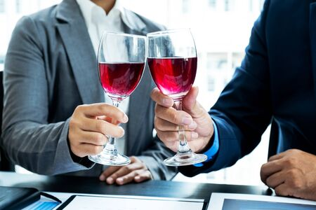 Two business executives people, businesswomen, and businessman in a suit is bumping into a glass of wine celebrating success at the office desk. After the meeting.
