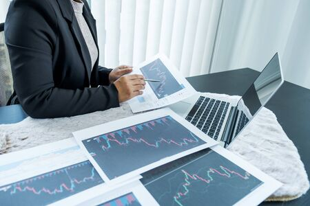 Businesswomen analyze stock graph and report, set targets for online trading management success.
