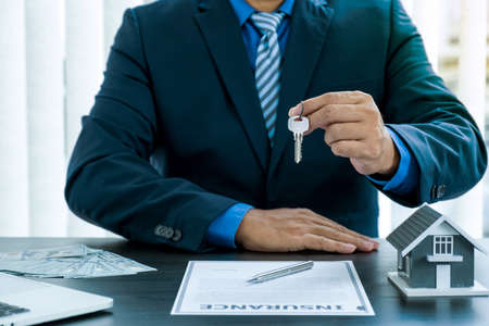 Hand a real estate agent, hold the keys, and explain the business contract, rent, buy, mortgage, loan, or home insurance. Banque d'images