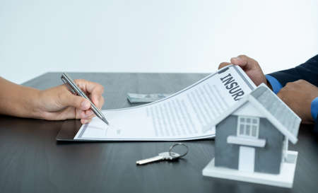 The buyer is signing a contract for business rental, mortgage purchase, or home insurance in front of a real estate agent.