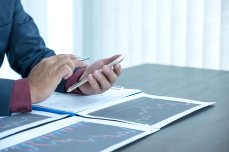 Trader businessmen analyze stock graph and report, set targets for online forex trading market management success.