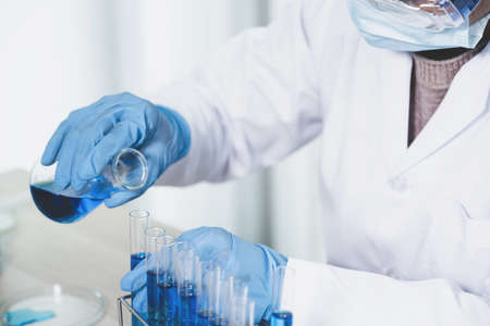Scientists hand hold a glass filled with blue chemical liquid for research and analysis in a laboratory.