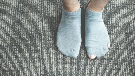 A pair of feet wearing old, dirty, and torn socks.