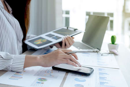 Businesswoman hand use smartphone and analysis the chart with laptop at the office for setting challenging business goals And planning to achieve the new target. Banque d'images