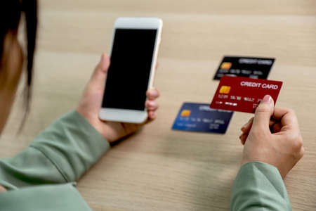 Businesswoman hand holding and use credit card to online shopping from home with smartphone, payment e-commerce, internet banking, spending money for next holidays.