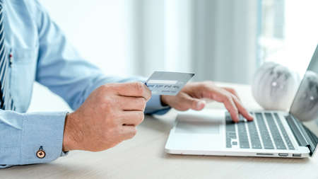 Businessman hand holding credit card to online shopping from home with laptop, payment e-commerce, internet banking, spending money for next holidays.