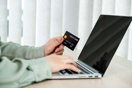 Businesswoman hand holding and use credit card to online shopping from home with laptop, payment e-commerce, internet banking, spending money for next holidays.