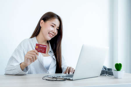 Businesswoman holding red credit card to online shopping from home, payment e-commerce, internet banking, spending money for next holidays.
