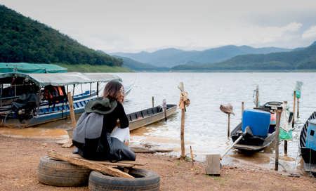 A beautiful tourist waiting for a boat With mountain water and sky as a backdrop. 版權商用圖片