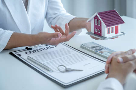 hand of the real estate agent explains the business contract, rent, purchase, mortgage, a loan, or home insurance to the women buyer.
