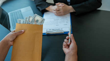 Businessman hand offer bribes money in envelope for signing in a contract of business project, Government officials refused, concept of corruption and anti bribery.