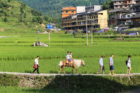villagers: Villagers riding on a horse in an ancient village in Guizhou