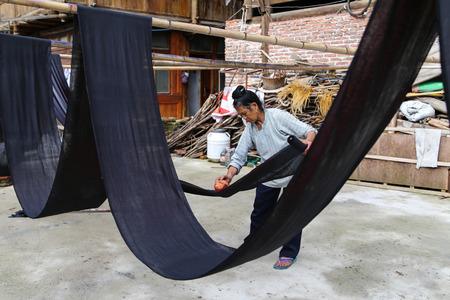 dyeing: woman dyeing clothes in zhaoxin,guizhou,china Editorial