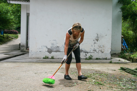foreigner: foreign volunteer cleaning in panda protection and research center of Yaan, Bifengxia base,china